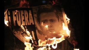 Demonstrators burn a sign with a photograph of Mexico's President Enrique Pena Nieto during a protest in support of the missing 43 trainee teachers in Mexico City December 1, 2014. The popularity of Pena Nieto has sunk amid concerns about his handling of security problems and corruption, polls showed on Monday, in a sign that his ruling party could lose ground in elections next year. Polls noted the sharp drop in his approval rating since the apparent massacre of 43 trainee teachers students and a conflict of interest scandal involving a home being purchased by the first lady. REUTERS/Carlos Jasso (MEXICO - Tags: CRIME LAW CIVIL UNREST EDUCATION POLITICS)